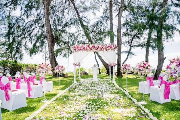 Arco da spiaggia per matrimoni, altare decorato con rose e fiori rosa, bianchi, rossi