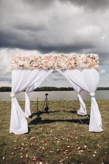 Arco di bel matrimonio con fiori vista sopra arco di matrimonio bianco con fiori in alto e petali di rosa sparsi sull'erba situato vicino al fiume in una giornata nuvolosa