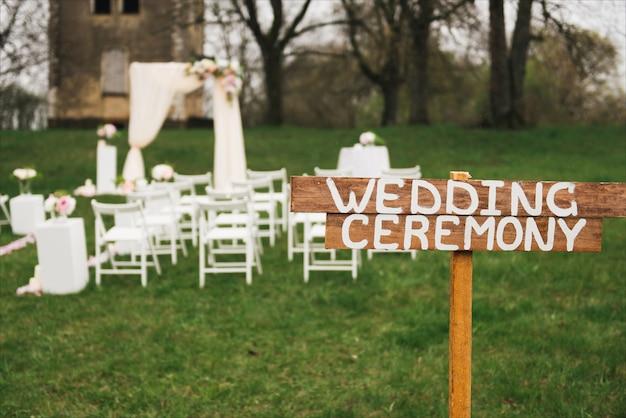 Arco di cerimonia nuziale decorato con il panno e fiori all'aperto. bel matrimonio allestito. cerimonia di nozze su prato inglese verde nel giardino. parte dell'arredamento festivo, composizione floreale.