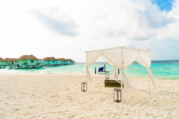 Arco di cerimonia nuziale sulla spiaggia con il ricorso e il mare tropicali delle maldive