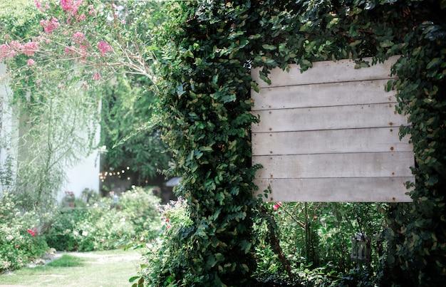 Arco di legno della pianta di verde dell'edera dell'intestazione al giardino