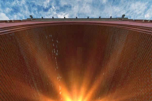 Arco di mattoni rossi. luce solare alla fine del tunnel.