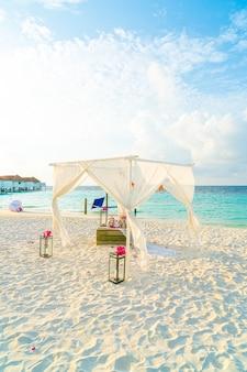 Arco di nozze sulla spiaggia con resort tropicale e mare delle maldive