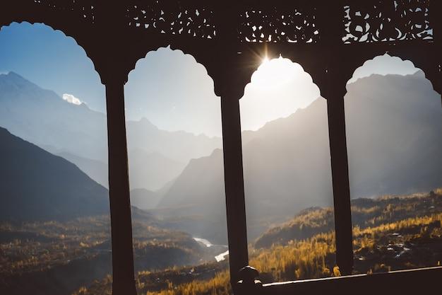 Arco in legno intagliato dell'antica fortezza di baltit, con sfondo sfocato della valle di hunza.
