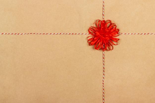 Arco rosso del regalo con i nastri sul fondo della carta del mestiere