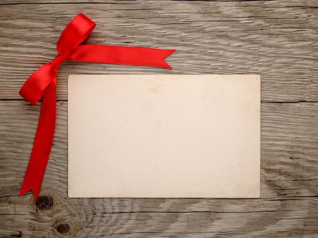 Arco rosso e cartolina d'epoca su fondo in legno vecchio