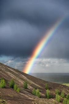 Arcobaleno in montagna contro un drammatico cielo tempestoso e nuvole