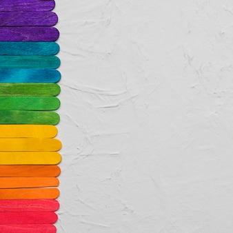Arcobaleno lgbt di bastoncini colorati su superficie grigia