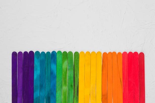 Arcobaleno lgbt di bastoncini di legno colorati sulla superficie grigia