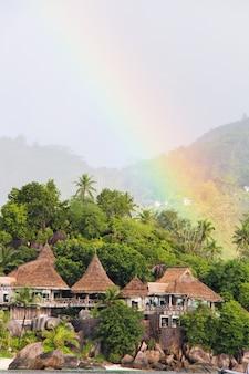 Arcobaleno sopra l'isola tropicale e l'hotel lussuoso