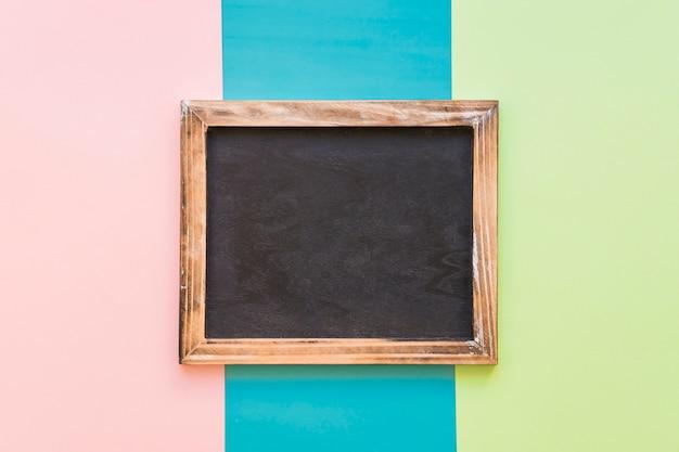 Ardesia con bordo di legno su sfondo colorato