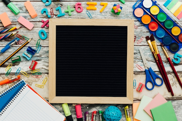 Ardesia con materiale scolastico su un tavolo di legno.