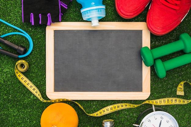 Ardesia di legno vuota con corda per saltare; nastro di misurazione; arancia; allarme; manubri; scarpe sportive; bottiglia d'acqua e guanti sul tappeto erboso