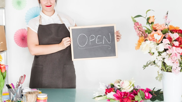 Ardesia femminile della tenuta del fiorista con la parola aperta in negozio floreale