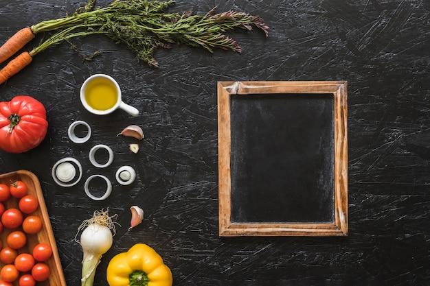 Ardesia in legno con ingredienti sul piano di lavoro della cucina