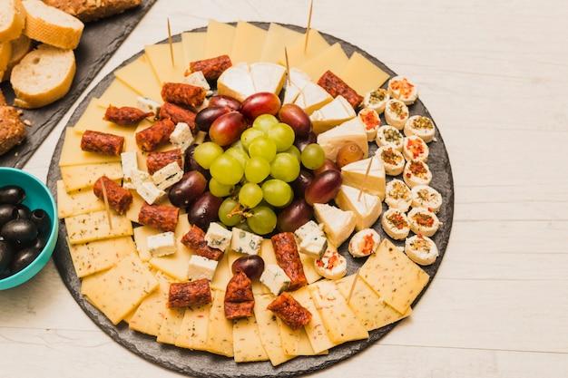Ardesia nera circolare con piatto di formaggi; uva e salsicce affumicate sul tavolo di legno