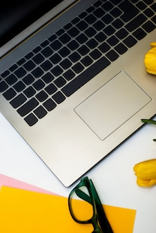 Area di lavoro a casa scrivania di posizione piatta alla moda con il computer portatile.