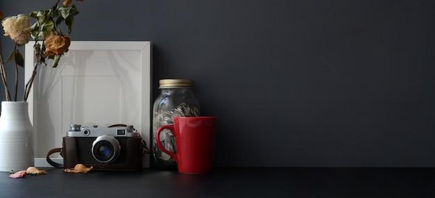 Area di lavoro alla moda scura con copia spazio e fotocamera sulla scrivania nera e parete grigio scuro
