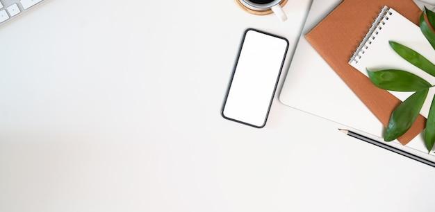 Area di lavoro bianca con forniture per ufficio, telefono cellulare schermo vuoto e copyspace