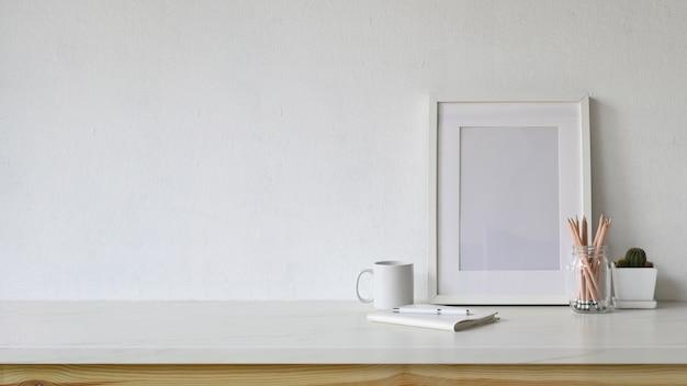 Area di lavoro bianca vuota poster e copia spazio con forniture per ufficio a casa.