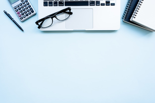 Area di lavoro con calcolatrice, penna, laptop, nota sullo sfondo blu pastello.