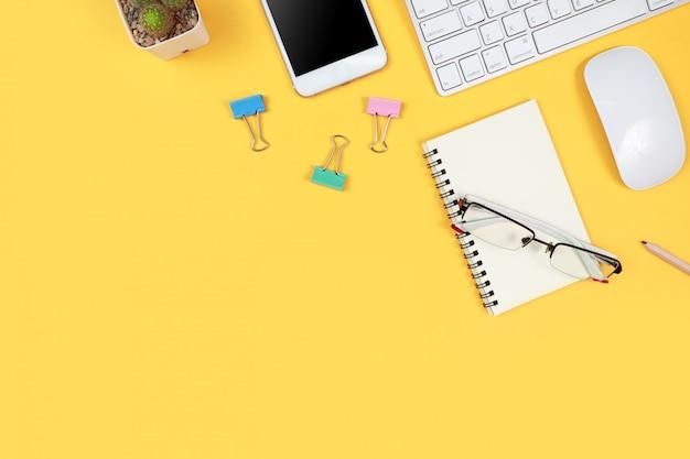 Area di lavoro con computer portatile e articoli per ufficio su giallo