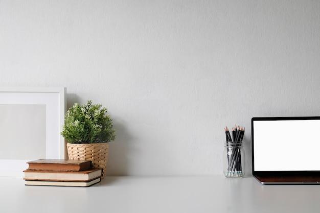 Area di lavoro con computer portatile e libro sul tavolo bianco.