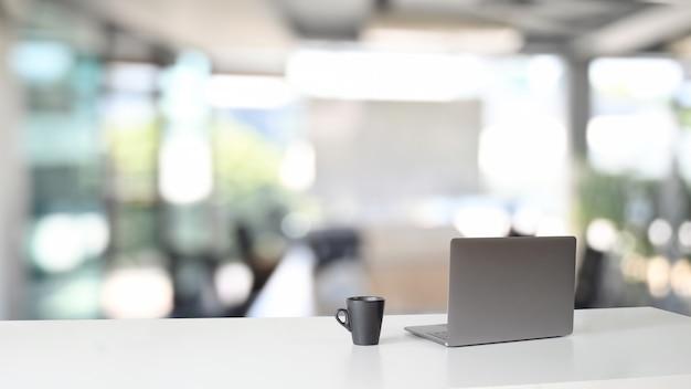 Area di lavoro con computer portatile e tazza di caffè sul tavolo.