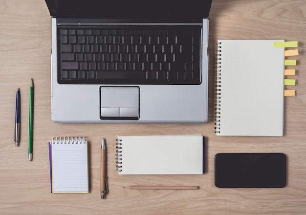 Area di lavoro con diario o notebook e appunti, laptop, matita, penna, note adesive, smart phone su legno