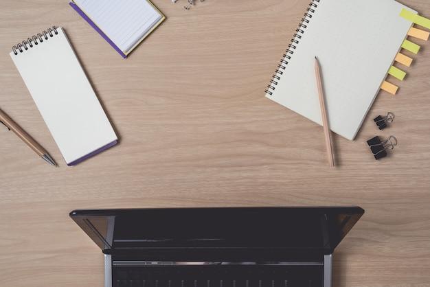 Area di lavoro con diario o notebook e appunti, laptop, matita, penna, note appiccicose su legno