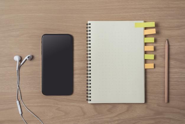 Area di lavoro con diario o notebook e smart phone, auricolare, matita, note adesive su legno