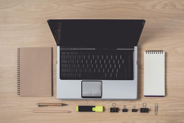 Area di lavoro con diario o taccuino e laptop, penna, matita, penna hightlight, clip in metallo su legno