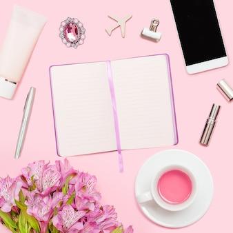 Area di lavoro con diario, penna, smartphone, rossetto, alstroemerias, tazza di tè, cosmetici