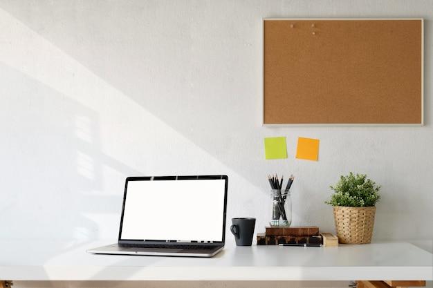 Area di lavoro con il computer portatile dello schermo in bianco sullo scrittorio di legno bianco.