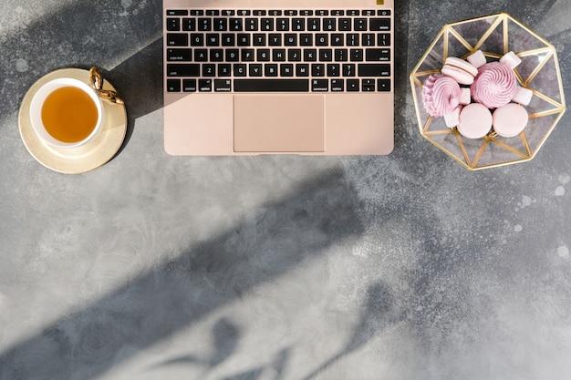 Area di lavoro con il taccuino, il tè e le decorazioni di rosa pastello su fondo grigio.