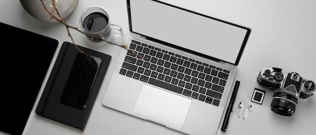 Area di lavoro con laptop, fotocamera, tablet, cancelleria, tazza di caffè e decorazioni mock-up