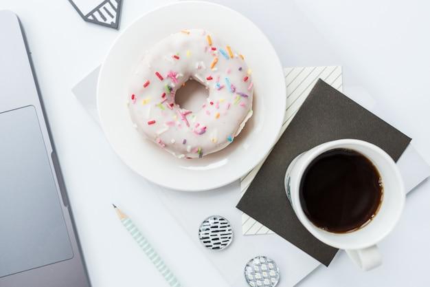 Area di lavoro con laptop, matita, quaderno, tazza di caffè e ciambella su sfondo bianco.
