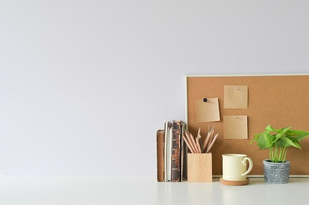 Area di lavoro con libri, caffè, pianta e carta per appunti appiccicosa a bordo ufficio scrivania bianca.