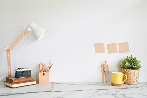 Area di lavoro con libri, macchina fotografica, lampada, caffè con pianta sulla scrivania di marmo.