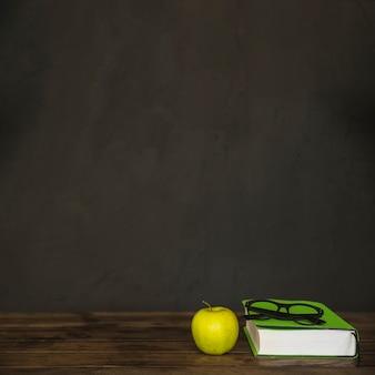 Area di lavoro con occhiali da libro e apple
