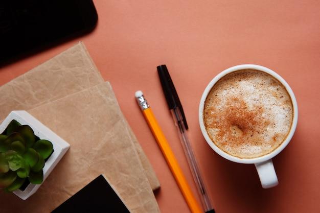 Area di lavoro con smartphone, forniture per ufficio e tazza di caffè su fondo di corallo.