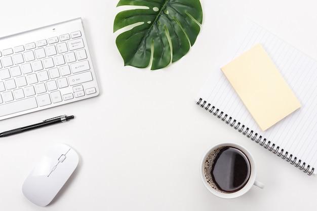 Area di lavoro con tastiera del computer, forniture per ufficio, foglia verde e tazza di caffè su sfondo bianco.