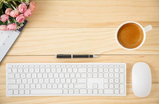 Area di lavoro con tastiera e mouse del computer bianchi e una tazza di caffè