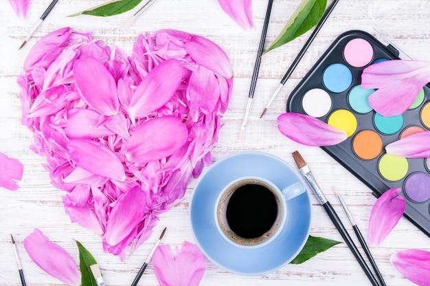 Area di lavoro con tazza di caffè e fiori