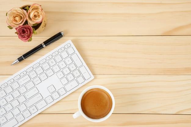 Area di lavoro con una tastiera di computer bianca e una tazza di caffè