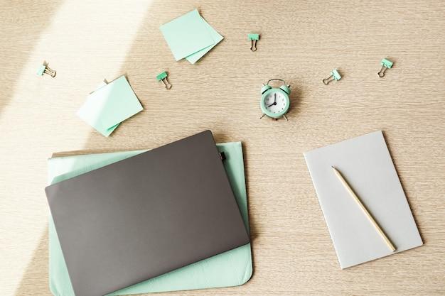 Area di lavoro confortevole per studenti, impiegati, liberi professionisti. desktop per formazione online, lavoro a distanza, lavoro da casa. computer portatile chiuso sulla tavola di legno leggera.