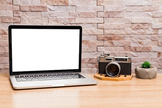 Area di lavoro creativa con laptop e fotocamera retrò