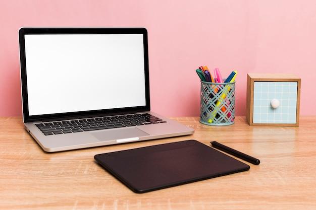 Area di lavoro creativa con laptop e tavoletta grafica
