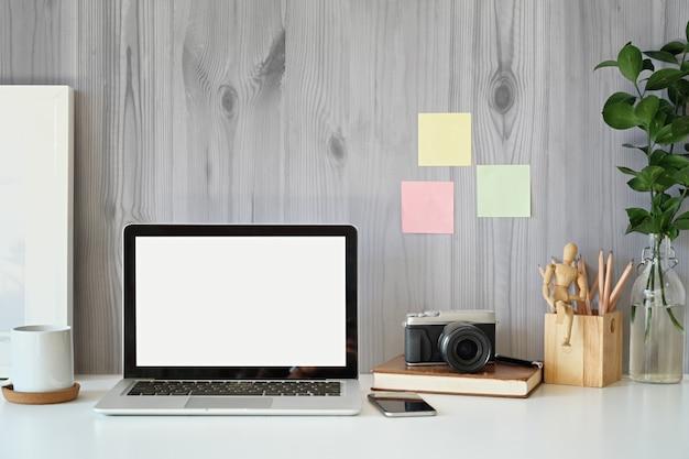 Area di lavoro creativo, laptop schermo vuoto, poster mockup e macchina fotografica d'epoca sulla scrivania