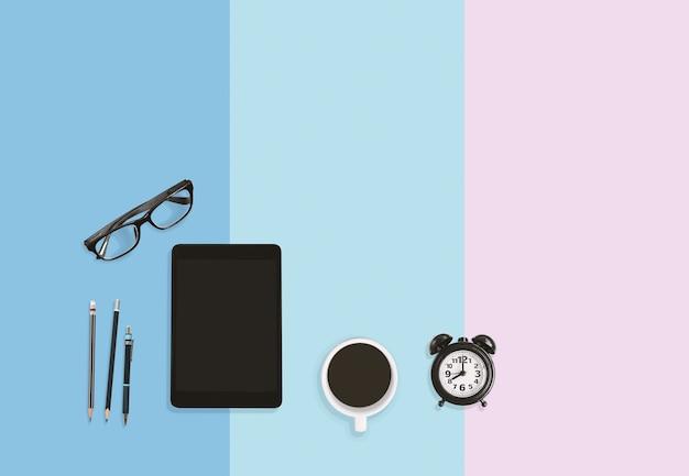 Area di lavoro da casa, sveglia, caffè, matite, occhiali e tablet su sfondo pastello